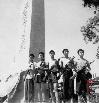 """1967年武斗停息后,在刚建成的重庆29中毛泽东主义战斗团死难同学""""烈士墓""""碑下,几个中学生手持冲锋枪留影,表示""""挥泪继承烈士志,誓将遗愿化宏图""""的""""决心"""""""