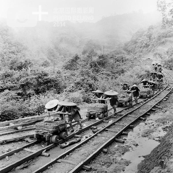 1960年夏季, 四川省李家山采矿场工人利用自创的独特运输方式在冒雨运输矿石。 新华社记者游云谷摄