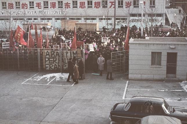"""1967年2月1日到5日,群众陆续到法国驻华使馆门前示威游行。此刻这个环境里的标语就像这个年代一样混乱。街对面的车库门上还有一列标语""""热烈欢迎解放军来(北京)参加接待红卫兵"""",这是上一年外地学生挤到北京等待接见,政府派军队参与接待并遣散人群的行动留下的印记"""