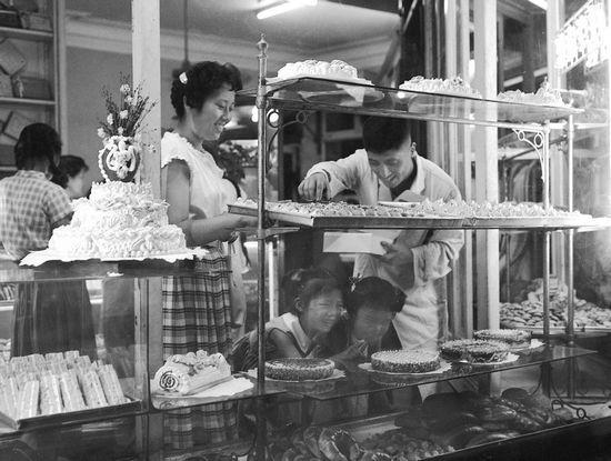 """1963年9月11日,新华社播发主题为""""上海市活跃的食品市场""""的照片,图释为""""在上海市著名的老大昌食品店里。"""""""